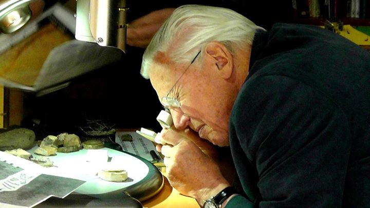 Sir David Attenborough examines fish fossils