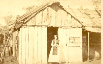 A woman standing in doorway of hut with bark roof, Gulgong 1872 or 1873, Holtermann Collection. Photo courtesy of National Library of Australia