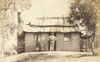 Man outside wattle and daub hut with bark roof, Hill End, New South Wales, circa 1872/3 From Holtermann archive of photographers Merlin and Bayliss. Source: National Library of Australia